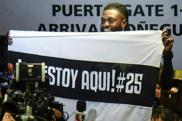Togo forward Emmanuel Adebayor holds up a message to his new fans at Paraguay champions Olimpia on his arrival in Asuncion - Hundreds of Olimpia fans welcome Adebayor to Paraguay