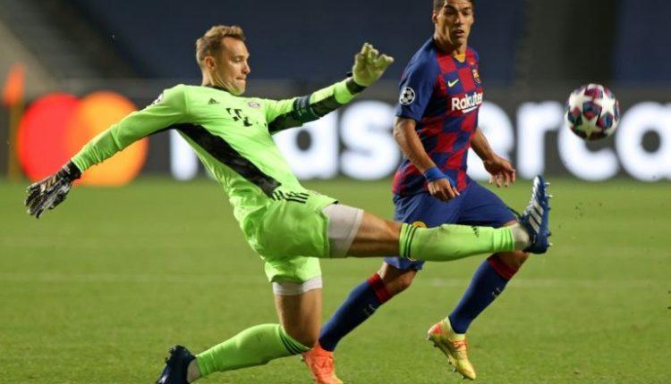 Bayern Munich goalkeeper Manuel Neuer (L) clears the ball against Barcelona.