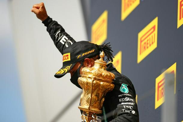 Champion Lewis Hamilton gestures on the podium after winning the 2020 British Grand Prix