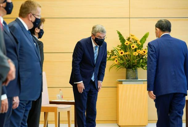 IOC president Thomas Bach (C) bows to Japan's Prime Minister Yoshihide Suga (R)