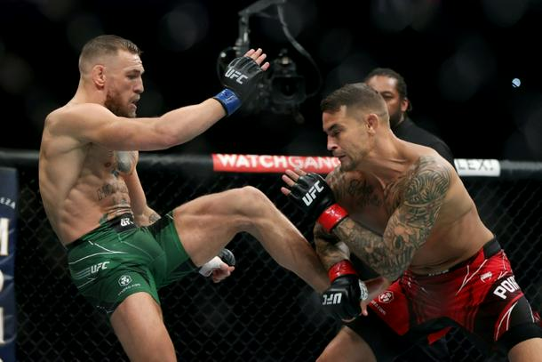 Ireland's Conor McGregor, left, launches a kick against Dustin Poirier in the first round in their UFC lightweight trilogy bout in Las Vegas
