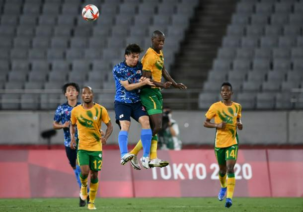 Japan midfielder Ao Tanaka jumps for a header with South Africa's Evidence Makgopa
