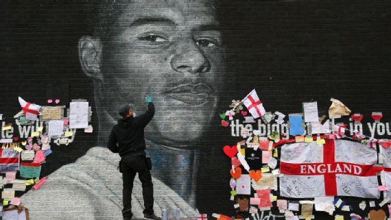 Street artist Akse fixes the Marcus Rashford mural after vandalism.