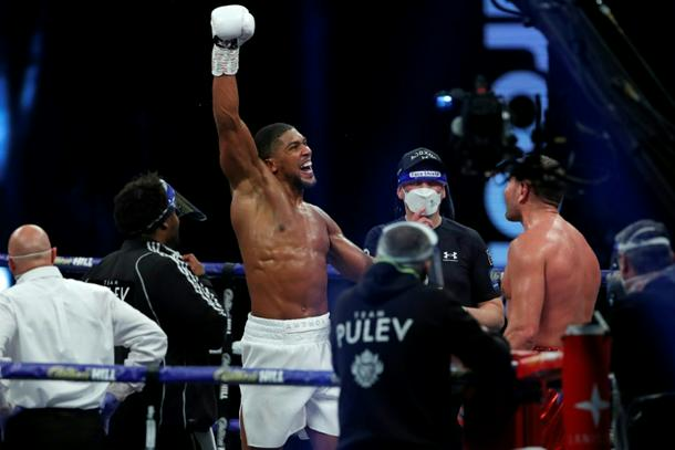 Anthony Joshua (L) pictured celebrating after his world heavyweight title win over Bulgaria's Kubrat Pulve at Wembley in December 2020